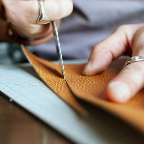Men's hands close-up cut a piece of genuine leather to make a wallet.
